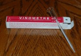 A vinometer is a piece of apparatus that consists of an open, graduated glass tube with a small filling resevoir.  The vinometer's reservoir or funnel is filled with a small amount of wine being tested until some wine exits out at the other end.